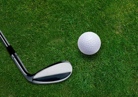 Golf ball and golf putter on green grass land . Stock Photo - 15551311