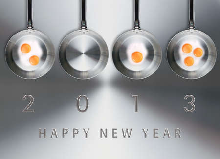fryer: Happy new year 2013, conceptual images Fried eggs in a frying pans creating 2013 year number. Stock Photo