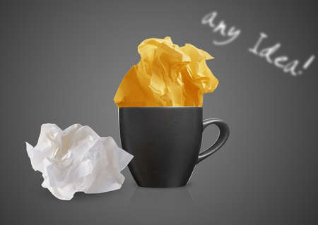 Crumpled colorful papers with coffee on black desktop.