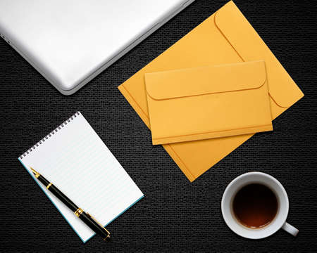 business desktop with laptop, notepad, envelops and coffee photo