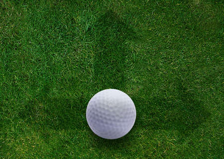 Golf ball on green grass land with green directions arrows.  Stock Photo - 15787565