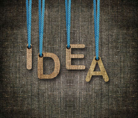 Idea word hunging by rope as puppeteer on sackcloth background. photo