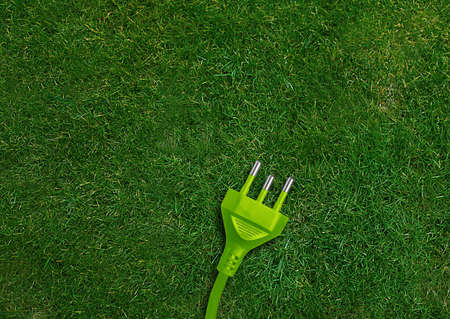 Green energy concept, Green power plug on a green grassland.  photo
