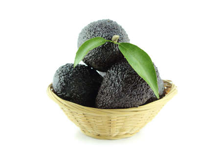 Avocados with leaves on a Dish of straw
