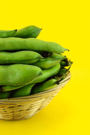 broad: broad bean pods and beans on yellow background .