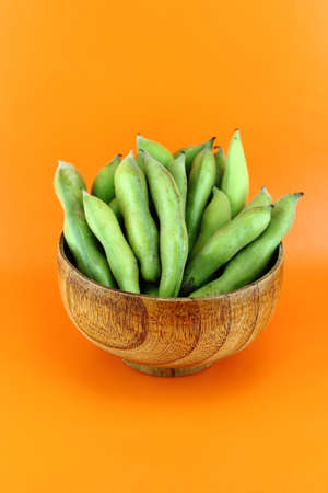 broad bean pods and beans on orange background . photo