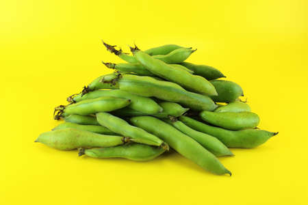 broad bean pods and beans on yellow background .