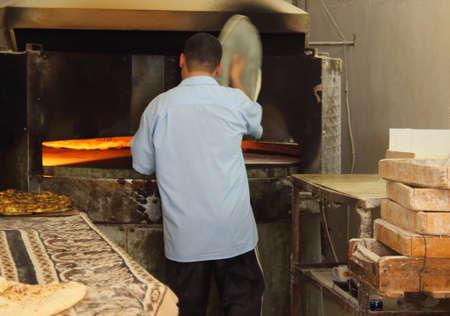 arab baker making arabic bread . photo