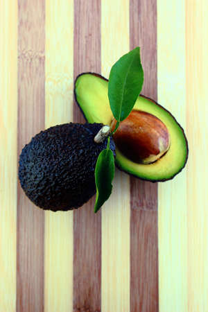 Black Ripe Avocados with leaves on wood Background.