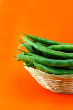 shuck: fresh beans fruit on orange background .