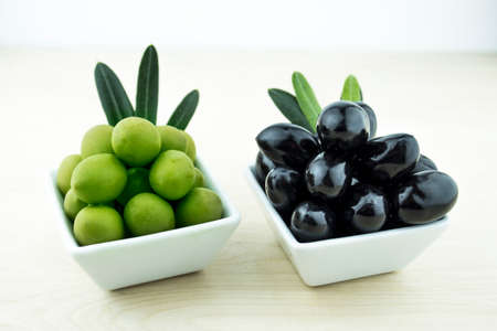 Black and Green Olives with leaves on a white background photo