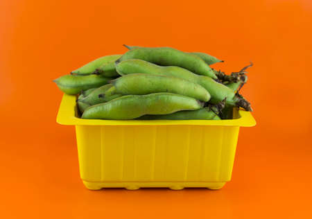 broad bean pods and beans on orange background .  Stock Photo