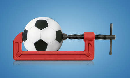 movable jaw: horizontal hand vise c-clamp and football, sport conceptual image