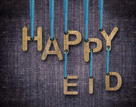 Happy Eid letters hanging strings with blue sackcloth background. Stock Photo