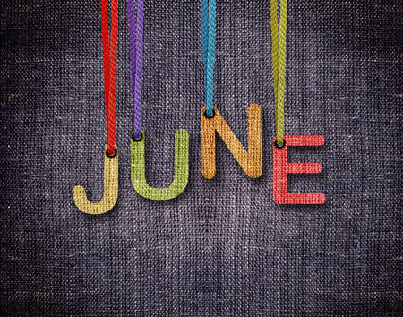 June letters hanging strings with blue sackcloth background.