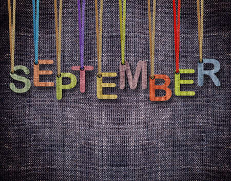 calendar september: September letters hanging strings with blue sackcloth background.