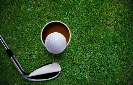 Golf ball and putter on green grass  Фото со стока