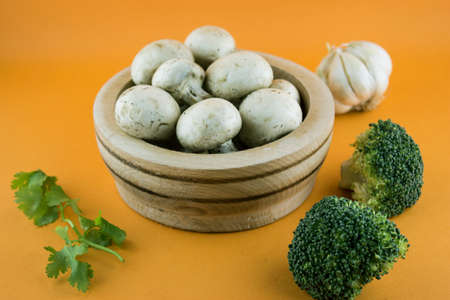 button mushrooms in wooden bowl with garlic, parsley and broccoli on orange background. photo