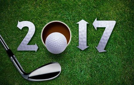 Frohes Neues Jahr 2017 Golf, Golfball und Putter auf grünem Gras.
