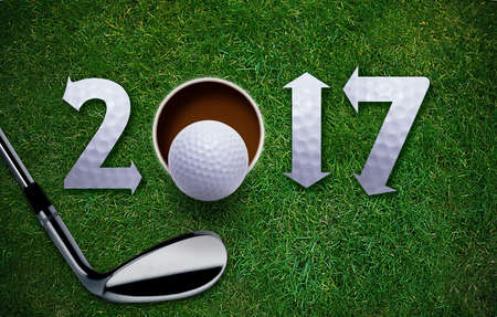 Happy New Golf year 2017,  Golf ball and putter on green grass.