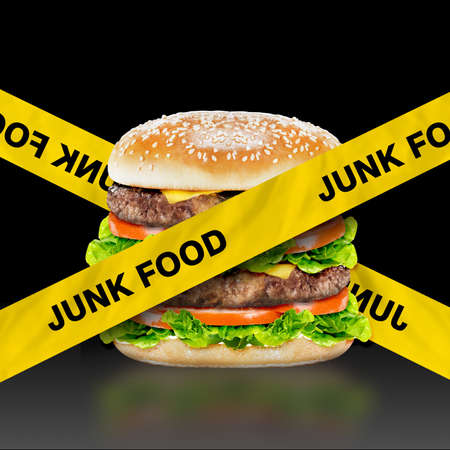 Junk Food, burger with warning message on black background  photo