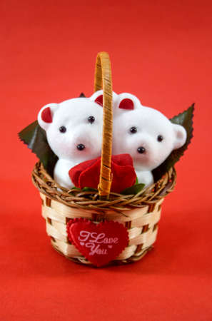 A cute white teddy bears with with rose in basket. photo