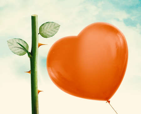 worse: Rose thorn about to pop love heart balloon in vintage blue sky, clipping path and alpha channel included. Stock Photo