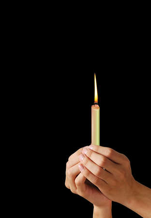 votive candle: Burning candle in woman hands on the black background