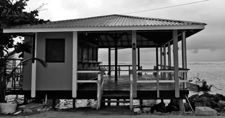 boathouse: Boat Tethered to the Platform of this Empty Beach Boathouse in the Harbor
