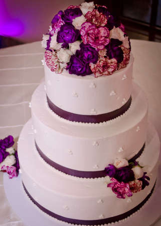 Tiered white wedding cake with purple flowers ribbon stock photo stock photo tiered white wedding cake with purple flowers ribbon mightylinksfo
