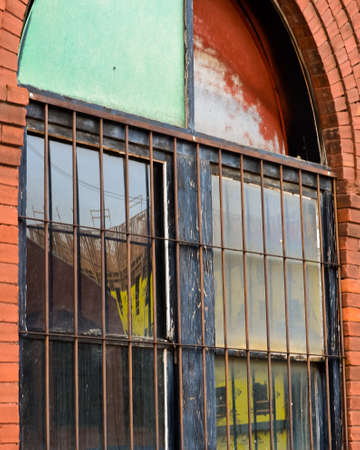 New Bricktown Construction Project Reflected in and Old Brick Building with Rusted Bars in Oklahoma City, Oklahoma