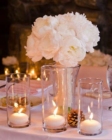 pfingstrosen: Weiß und rosa Pfingstrosen-Hochzeits-Blumenstrauß in einer Vase von Kerzen und Kieferkegel auf einem Tisch mit Akzent
