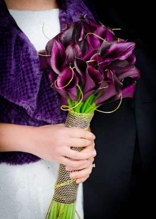 embellishments: Hands Holding Purple Calla Lilly Bridal Bouquet with Gold Embellishments Stock Photo