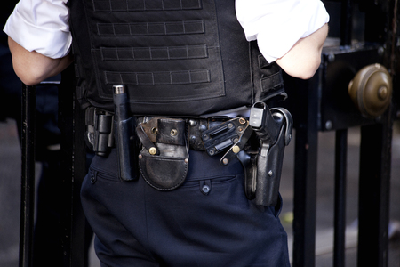 body guard: A close up of the belt and weapon of a British armed Police officer outside the gates of Downing Street, London, UK.
