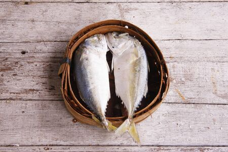 Mackerel fish in bamboo basket on wooden table photo