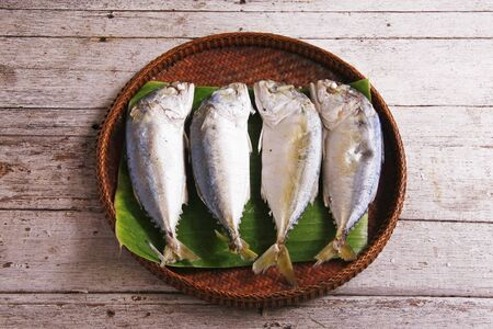 Mackerel fishes in bamboo basket on wooden table photo