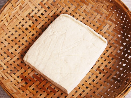 tofu in the threshing basket on wooden table photo