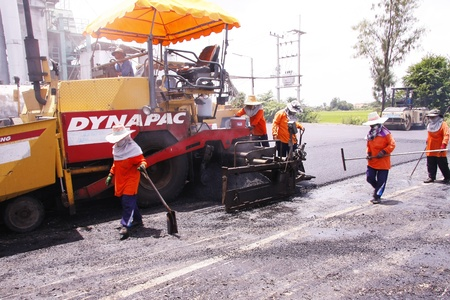 vibroroller: LOP BURI,THAILAND - AUGUST 3  Workers operating asphalt paver machine and heavy machinery during repairs road under the  program repairs road in asphalt plant on August 3,2013 in Lop Buri,Thailand