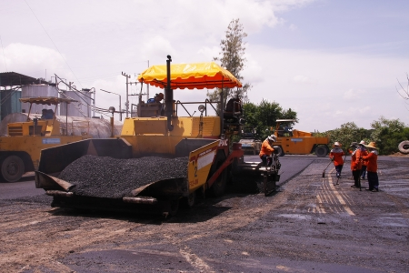 construction vibroroller: LOP BURI,THAILAND - AUGUST 3  Workers operating asphalt paver machine and heavy machinery during repairs road under the  program repairs road in asphalt plant on August 3,2013 in Lop Buri,Thailand
