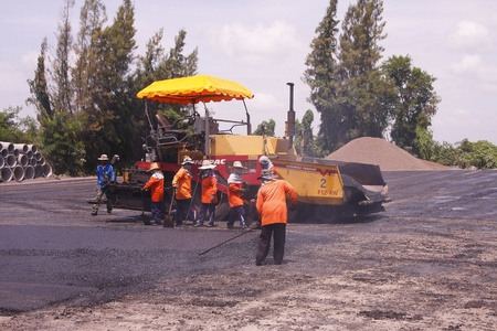LOP BURI,THAILAND - AUGUST 3  Workers operating asphalt paver machine and heavy machinery during repairs road under the  program repairs road in asphalt plant on August 3,2013 in Lop Buri,Thailand