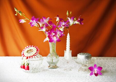 still life with glass bowl,vase,orchid,si lver bowl,glass tray with pedestal,candle and jasmine garlands  photo