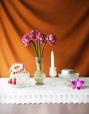 still life with glass bowl,vase,lotus,silver bowl,glass tray with pedestal,candle and jasmine garlands  photo