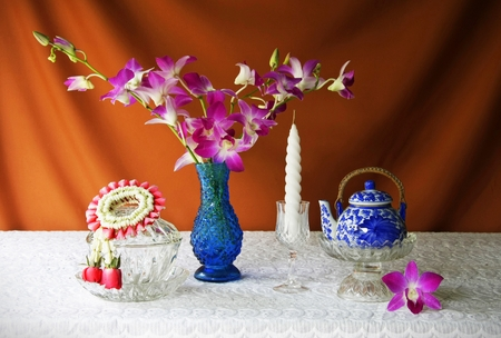 still life with glass bowl,vase,orchid,glass tray with pedestal,candle,tea pot and jasmine garland   photo