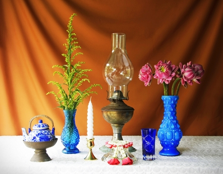 still life with lamp,teapot,vase,brass tray with pedestal,garland and candle  photo