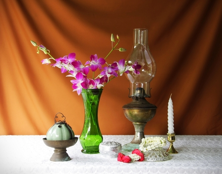 still life with vase,lotus,lamp,brass tray with pedestal,silver bowl, orchid,candle and garland  photo