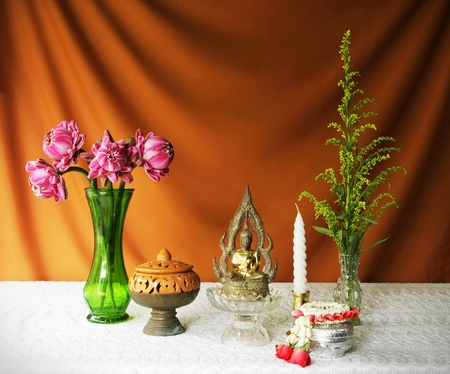 still life with buddha statue,vase,lotus,brass tray with pedestal,earthen bowl,garland and candle  photo