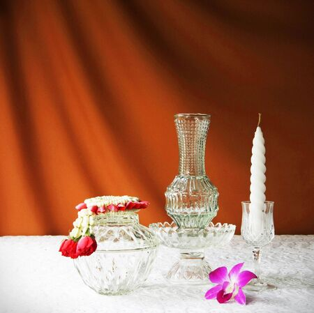 glass bowl, vase, orchid, glass tray with pedestal ,candle and jasmine garland  photo