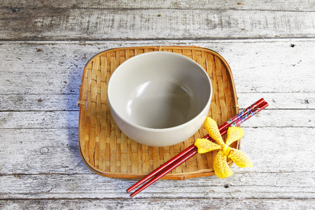 ceramic bowl and chopsticks in bamboo tray on wooden table photo