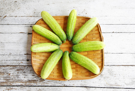 still life with Cucumbers in the threshing basket on wooden table  photo
