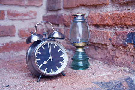 still life with vintage retro alarm clock and oil lamp with old brick wall background photo